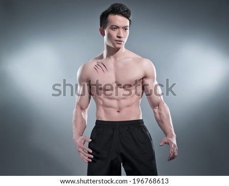 Muscled asian kung fu man in action pose. Blood stripes on his chest. Wearing black pants. Studio shot against grey.