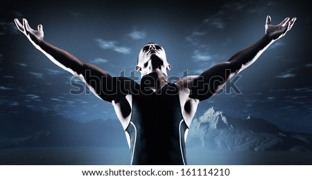 Muscled fitness triathlon athlete. Arms spread wide. Victory. Standing in desert at night.