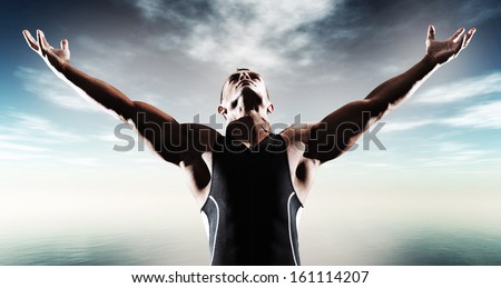 Muscled fitness triathlon athlete. Arms spread wide. Victory. Standing near lake.