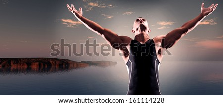 Muscled fitness triathlon athlete. Arms spread wide. Victory. Standing near lake at sunset.
