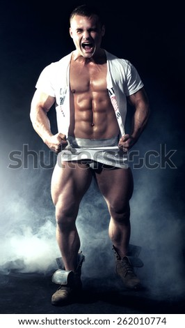Muscled handsome man posing in studio, emotional male model. - stock photo