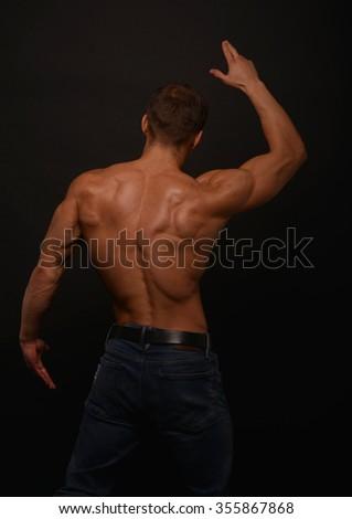 Muscled male model in studio - stock photo