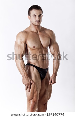 Muscled male model posing in studio on white background