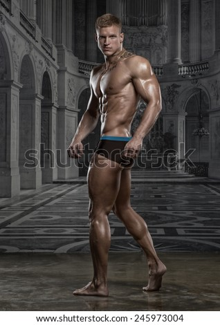 Muscled male model posing on palace wallpaper background  - stock photo