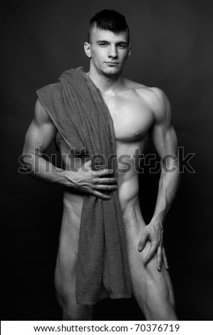 Muscled male model posing with a towel - stock photo