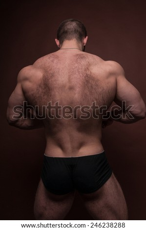 Muscled male model with body hair - stock photo