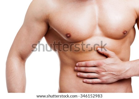 Muscled man holding his belly in pain, isolated on white background