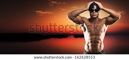 Muscled swimmer man with cap and glasses outdoor at a lake at sunset. Extreme fitness sport.