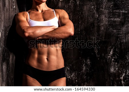 Muscled woman against the scratched grunge background - stock photo