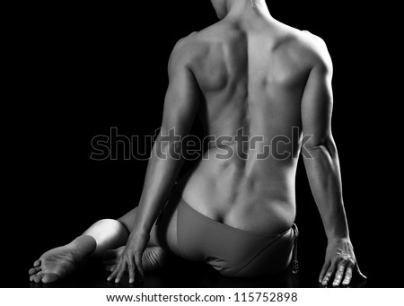 Muscled woman sitting on black floor - stock photo