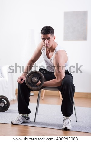 Muscled young man lifting heavy dumbbell at home