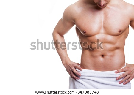 Muscled young man posing in towel, isolated over white background