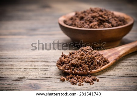 Muscovado sugar on old wooden table - stock photo