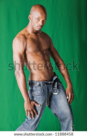 Muscular  African american man with blue jeans, on a green background - stock photo