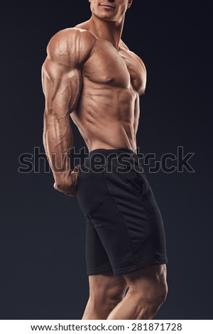 Muscular and fit bodybuilder fitness male model posing over black background. Strong and handsome young man demonstrate his muscular torso and biceps. Body of muscular male with great physique - stock photo