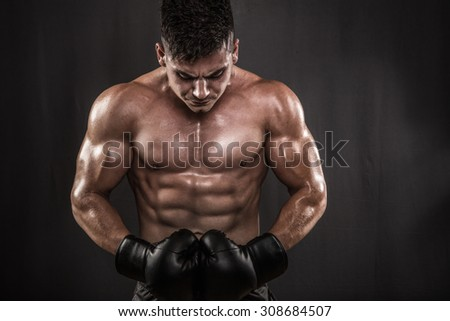 Muscular and fit male posing in studio with boxing gloves.