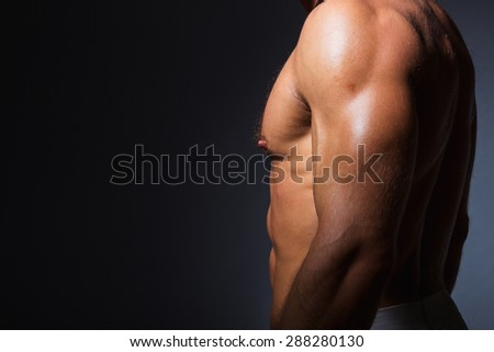 Muscular and fit torso of young sporty man showing his perfect triceps muscles. Dramatic light - stock photo