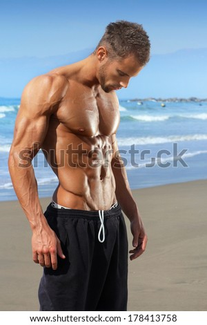 Muscular and fit young bodybuilder fitness male model on beach - stock photo