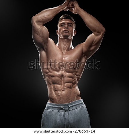 Muscular and fit young bodybuilder fitness male model posing over black background. - stock photo