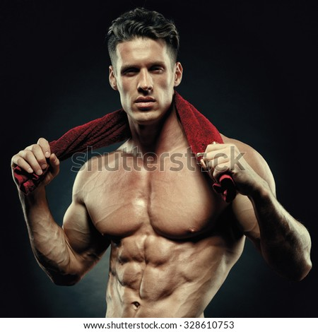 Muscular and fit young bodybuilder fitness male model posing over black background.