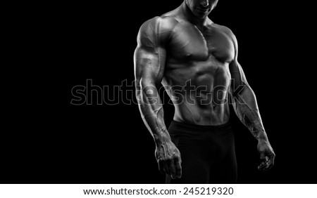 Muscular and fit young bodybuilder fitness male model posing over black background. Black and white photo with copy space - stock photo