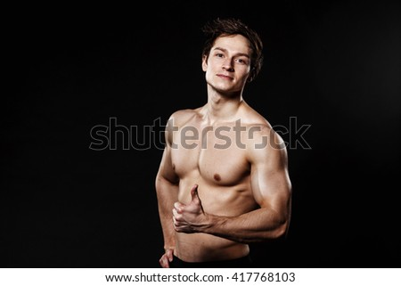 Muscular and fit young bodybuilder fitness male model showing thumb-up and posing over black background. Perfect fitness body. Ideal for commercial.