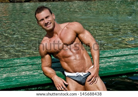 Muscular and fit young bodybuilder leaning on green wood planks on the sea - stock photo