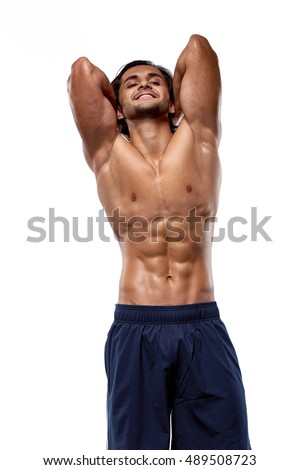 Muscular and fit young bodybuilder posing demonstrates the core muscles. Isolated on white background.