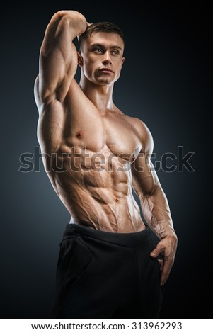 Muscular and fit young fitness male model posing over black background. Strong bodybuilder with six pack, perfect abs, shoulders, biceps, triceps and chest.