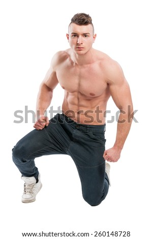 Muscular and handsome male model on one knee isolated on white background - stock photo
