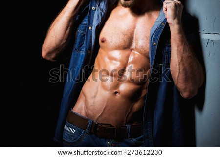 Muscular and sexy body of young sporty man in jeans shirt with perfect abs - stock photo