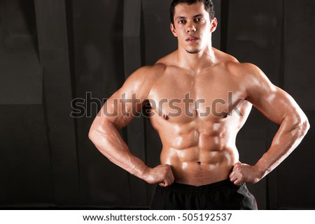 Muscular and sexy torso of young man with perfect abs and chest on black background.