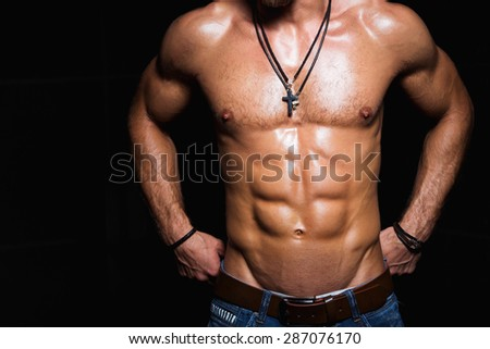 Muscular and sexy torso of young sporty man bodybuilder in jeans with perfect abs, bicep and chest - stock photo