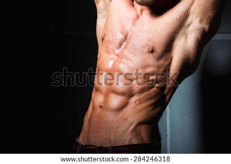 Muscular and sexy torso of young sporty man bodybuilder with perfect abs - stock photo