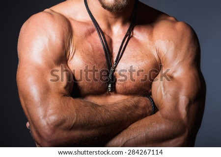 Muscular and sexy torso of young sporty man showing his perfect bicep and body - stock photo