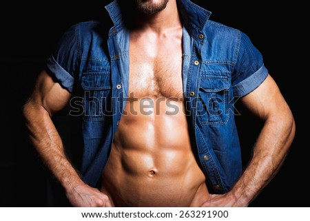 Muscular and sexy young man in jeans shirt with perfect body - stock photo