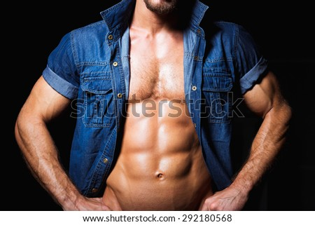 Muscular and sexy young man in jeans shirt with perfect body close up - stock photo