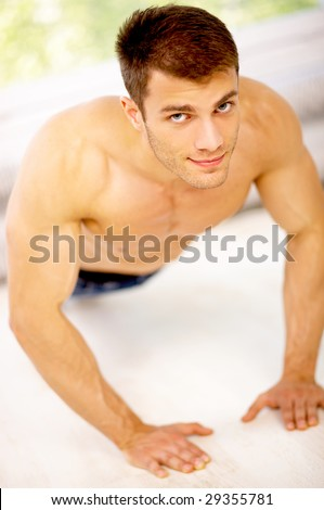 Muscular and tanned male is exercising, wearing jeans - stock photo