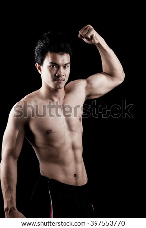 Muscular Asian man show his body on dark background