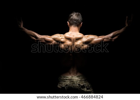 Muscular athlete bodybuilder man in camouflage pants with a naked torso on a dark background
