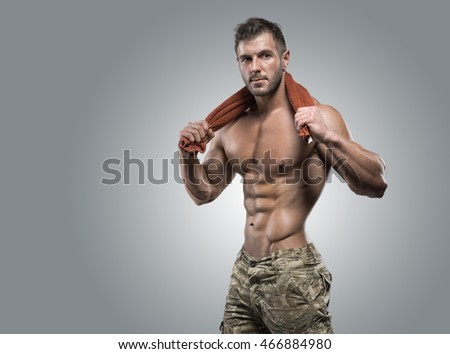 Muscular athlete bodybuilder man in camouflage pants with a naked torso on a gray background