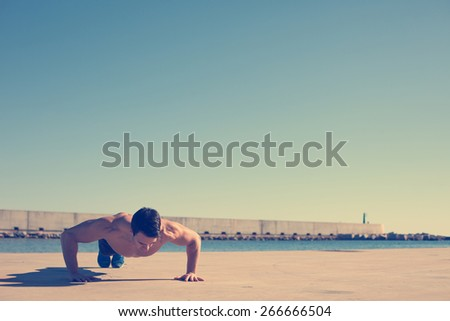 Muscular athlete doing jumping push-ups outdoors in the park near water (intentional vintage color - stock photo