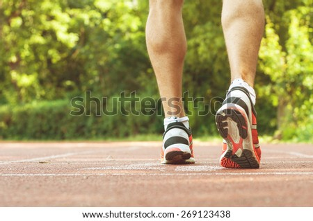 Muscular athlete legs waiting at the starting line on the race track with retro instagram filter. Runner training hard for winning competition. Concept of doing sports and living a healthy lifestyle. - stock photo