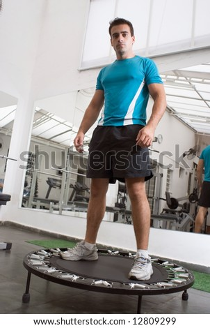 Muscular athlete, looking into the camera, standing on trampoline in a gym. - stock photo