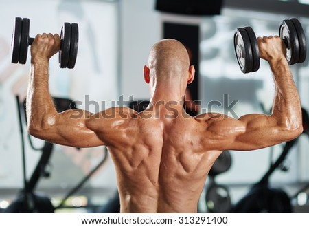 Muscular athlete shirtless doing triceps and shoulder workout with dumbbells - stock photo