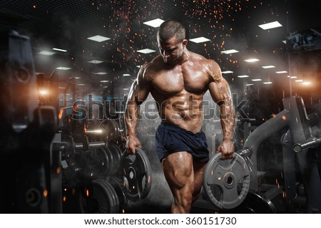 Muscular athletic bodybuilder fitness model posing after exercises in gym - stock photo