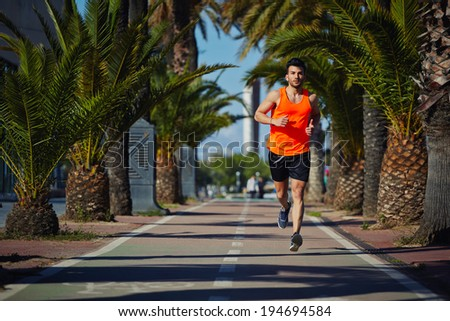 Muscular athletic man in the bright sportswear running on the jogging track - stock photo