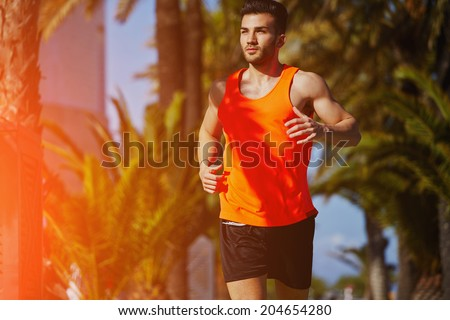 Muscular athletic man running on the jogging track on the palm trees background, male runner on the evening jog, fitness and healthy lifestyle concept - stock photo