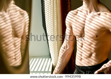 Muscular athletic man stands near the window in the morning