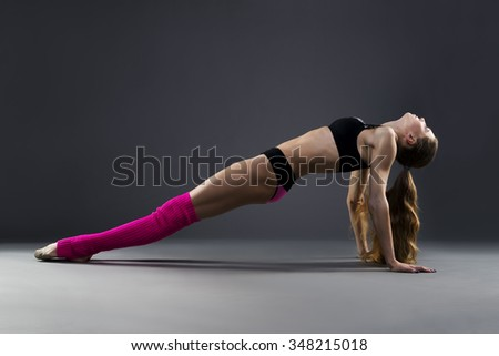 Muscular attractive fitness woman warming up in the studio on gray background. Flexible dancer - stock photo